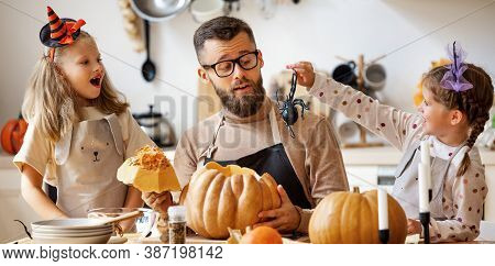 Bearded Man And Girls With Jack O Lantern Smiling And Scare Each Other With A Spider  During Prepara