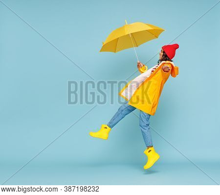 Side View Of Happy Ethnic Woman In Outerwear And With Umbrella Leaping And Having Fun On Rainy Autum