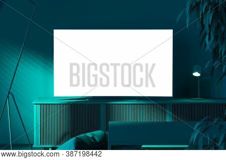 Blank White Tv Set On Cupboard Near Big Plant. Drawing Room Lit By Green Light, 3d Rendering. Living