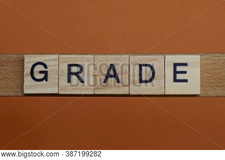 Gray Word Grade Made Of Wooden Square Letters On Brown Background