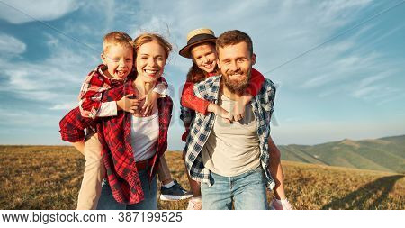 Happy Family: Mother, Father, Children Son And  Daughter Hugging, Laughing And Having Fun On Grass,