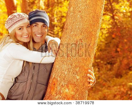 Picture of happy people spending fun time together in beautiful autumn park, closeup portrait of attractive female and handsome male smiling, young adult couple enjoying outdoor, love concept