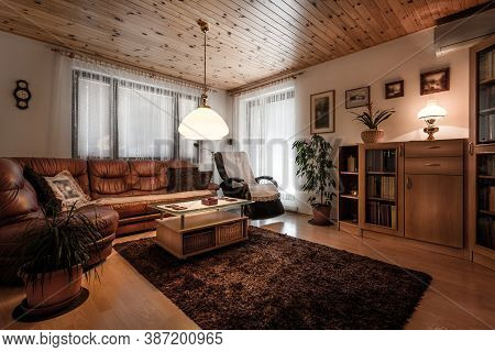 Classically Furnished Living Room In Wooden Design With Old Fashioned Accessories Like Lights, Woode