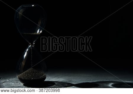 Hourglass On Dark Background, Close Up. Urgency And Running Out Of Time Concept
