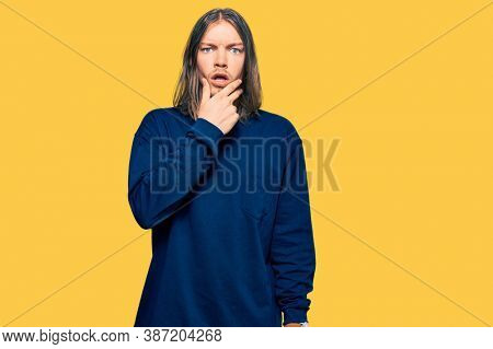 Handsome caucasian man with long hair wearing casual winter sweater looking fascinated with disbelief, surprise and amazed expression with hands on chin