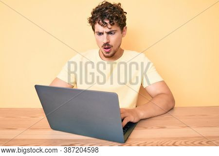 Young caucasian man with curly hair working at the office with laptop scared and amazed with open mouth for surprise, disbelief face