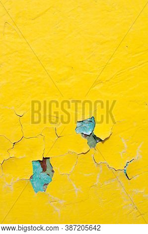 Texture background of bright yellow and blue peeling paint on the old rough texture surface. Peeling yellow paint background, texture pf peeling paint