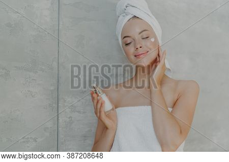 Pretty Young Woman Holds Bottle Of Body Lotion, Applies Face Cream On Complexion, Stands With Closed