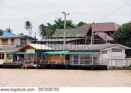 Village Beside Chaophraya River, It Is Thai Local Waterfront Community Life. A Group Of Houses And A