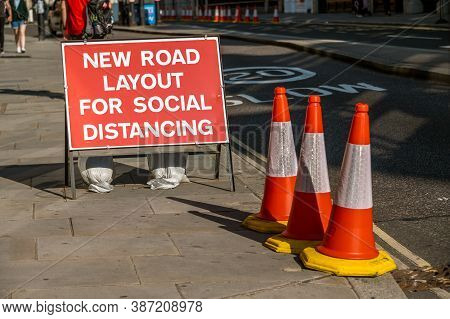 London - September 13, 2020: A Uk Road Sign With Orange Traffic Cones Telling Users That The Layout