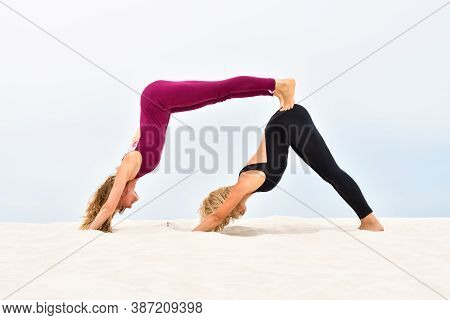 Two Beautiful Young Women Performing Steamy Yoga Standing On The Sand