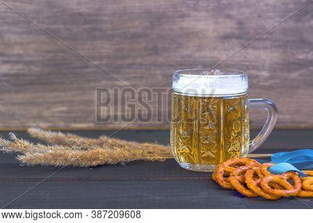 October Fest Concept. Beer Mug With Snacks Of Salt Pritzels, Bretzel And Blue Tape On Dark Wooden Ba