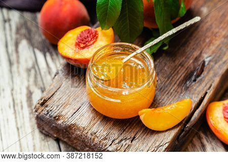 Peach Jam In Glass Jar With Peach Wedges And Whole Peach Fruit. Peach Jam On Wooden Table. Top View