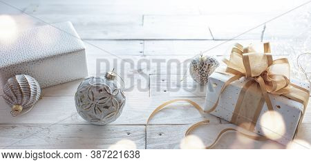Gift With Golden Ribbon Bow And Christmas Baubles On White Wooden Vintage Background. Horizontal Clo