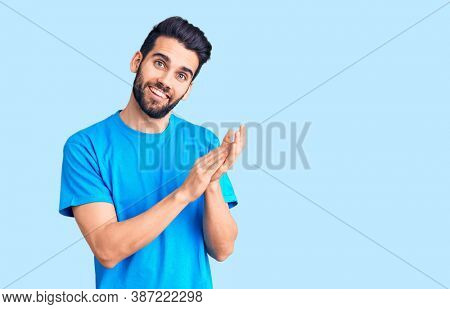 Young handsome man with beard wearing casual t-shirt clapping and applauding happy and joyful, smiling proud hands together