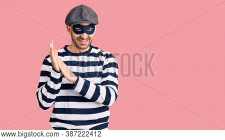 Young handsome man wearing burglar mask clapping and applauding happy and joyful, smiling proud hands together