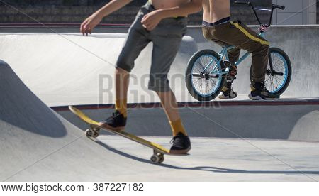 Young Active Teenagers Riding Stunts On Skateboard And Bmx Bike In Skatepark