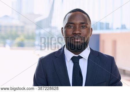 Young African businessman in elegant suit with tie standing in front of camera against group of modern buildings in urban environment