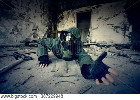 Post apocalyptic survivor in gas mask asking for help in a ruined building. Environmental disaster, armageddon concept.
