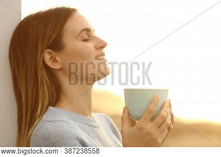 Relaxed Woman Drinking Coffee Resting Leaing On A Wall On The Beach At Sunset