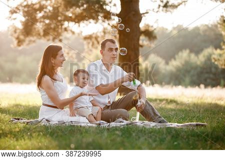 Father, Mother And Son Blow Soap Bubbles In The Park Together On A Sunny Summer Day. Happy Family Ha