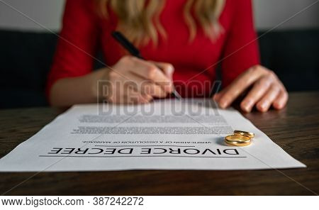 Wife Signing Decree Of Divorce Agreement Prepared By Lawyer.