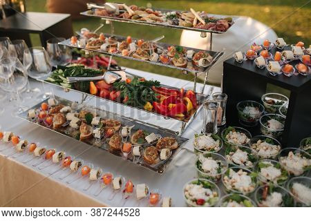 Big Table With Different Luxury Snacks On The Deluxe Party Outdoors In Sunset