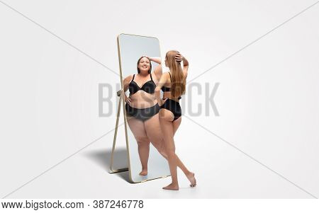 Young Fit, Slim Woman Looking At Fat Girl In Mirrors Reflection On White Background. Thinking Shes N