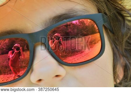 Reflection Of The Photographer In The Sun Glasses Of A Girl During A Summer Day