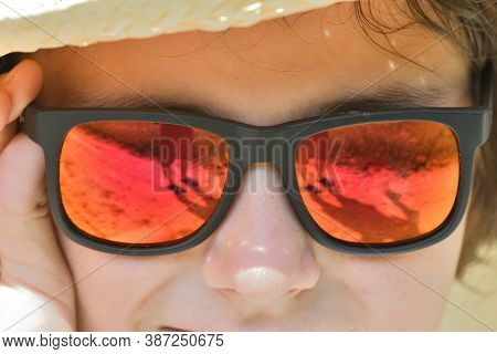 The Girl\'s Face And The Reflection Of A Man With A Camera In Her Sun Glasses