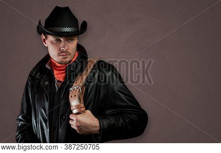 Unshaven Man In A Hat And Cloak. Cowboy In Leather Clothes With A Belt In His Hands. Macho Guy On Th