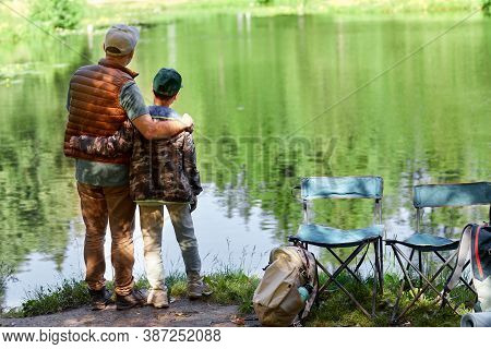 Full Length Back View Portrait Of Father And Son Standing By Lake And Enjoying Nature During Hiking