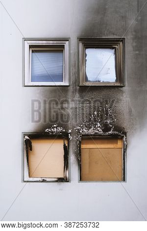 House Or Home Fire - Boarded Up Windows And Burned Facade Blackened By Soot Of Modern Multi Story Ap