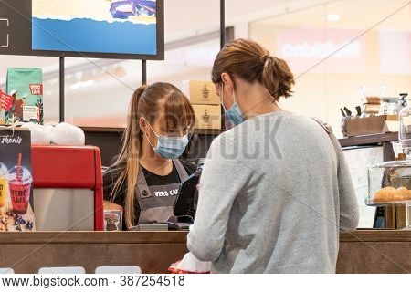 Vilnius, Lithuania - September 28 2020: Pretty Young Waitress With A Mask And Gloves Serving Client