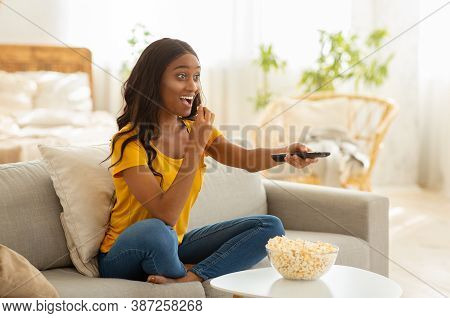 Pretty African American Lady With Tv Controller Enjoying Interesting Movie At Home, Blank Space. You