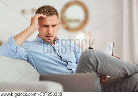 Planning And Project. Portrait Of Focused Pensive Man Working From Home, Sitting On Couch, Holding N
