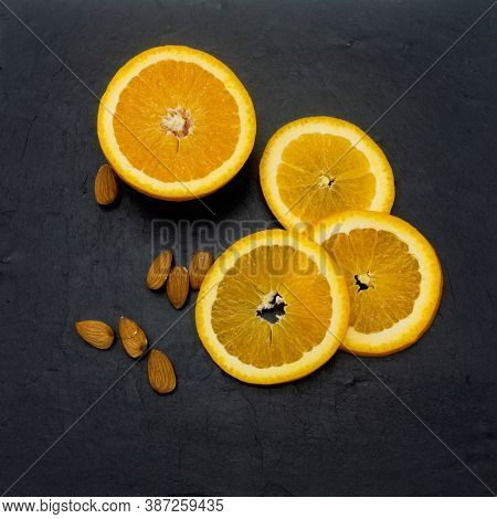 Sliced Orange On The Background Of Black Stone Tiles. Half The Fruit And Three Slices Lie In A Semic