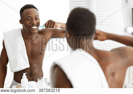 African American Guy Cleaning Teeth With Toothbrush Standing Near Mirror In Modern Bathroom At Home