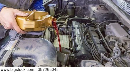 Mechanic Topping Up The Oil In A Car Pouring A Pint Of Oil Through A Funnel Into The Engine, Close U