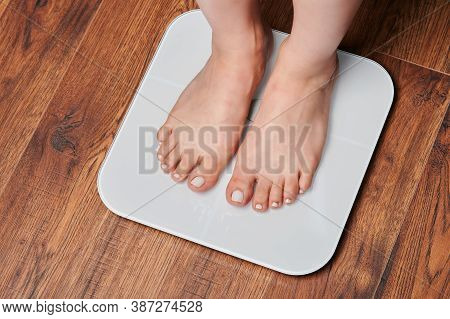 Woman Feet On White Scale In Wooden Floor Background