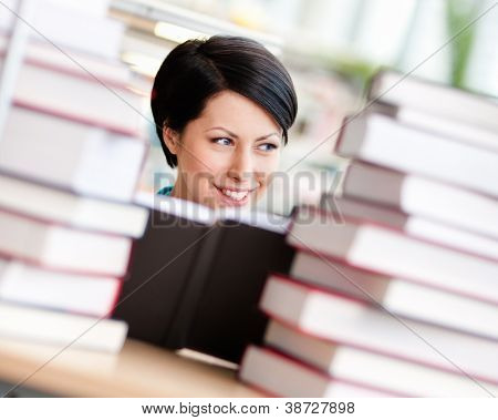 Female student sitting at the desk is surrounded with piles of books. Educational process