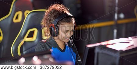 Focused Professional Female Cybersport Gamer Wearing Headphones Playing Online Video Games, Particip