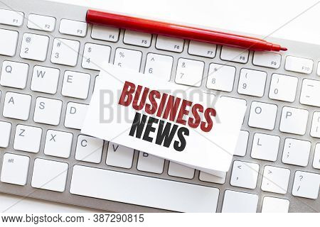 Words Business News Written On Torn Paper On A Computer Keyboard