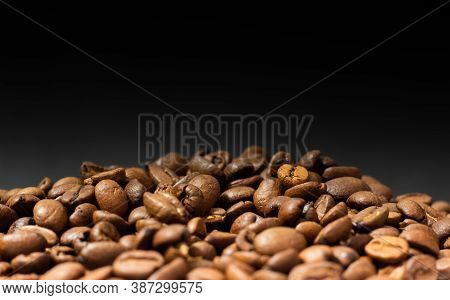 Roasted Coffee Beans On Black Background. Heap Of Coffee Beans. Poured Coffee Close-up