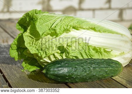 On A Wooden Board Are Vegetables Cucumber And Peking Cabbage