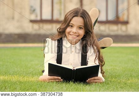 Basic Education. Extracurricular Reading. Cute Small Child Reading Book Outdoors. Adorable Little Gi