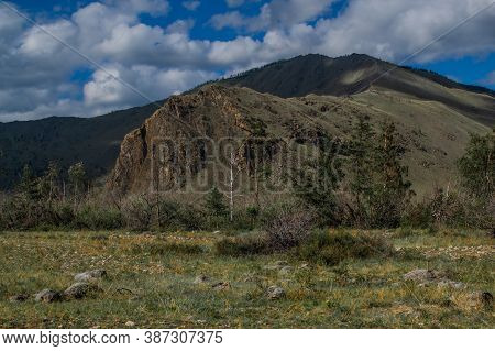Large Tall Green Grassy Rock. Mountain Range On Baikal, Sarma. Trees And Bushes In The Foreground In