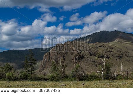 Large Tall Rock, Peak. Mountain Range On Baikal, Sarma. Trees And Bushes In The Foreground In Dry St