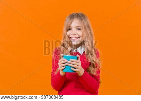 Health And Healthy Drink. Child Smile With Blue Cup On Orange Background. Girl With Long Blond Hair