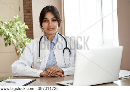Confident Indian Female Doctor Wear White Medical Coat, Stethoscope Look At Camera Sit At Workplace.